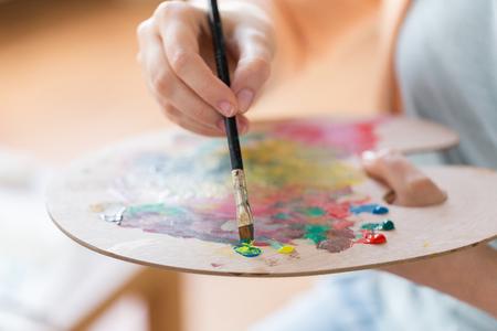 Concepto de arte, creatividad y personas - cerca del artista con pintura de paleta, pincel y caballete en el estudio Foto de archivo - 93050796