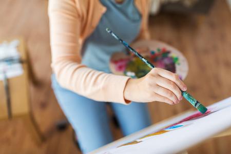 アート、創造性、人々のコンセプト - パレットとペイントブラシの絵画静物をスタジオで紙に描くアーティストのクローズアップ