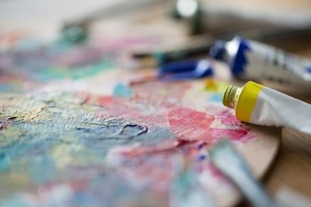 fine art, creativity, painting and artistic tools concept - close up of acrylic color or paint tubes and palette 스톡 콘텐츠