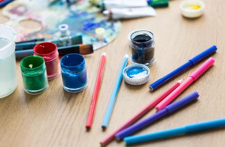 fine art, creativity and artistic tools concept - gouache colors, felt tip pens and pencils on table