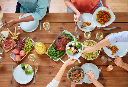 thanksgiving day, eating and leisure concept - group of people having dinner at table with food 스톡 콘텐츠
