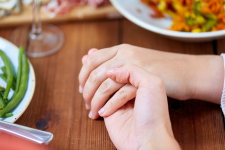 people, relationships and eating concept - hands of people sitting at table with food and praying before meal Stock Photo