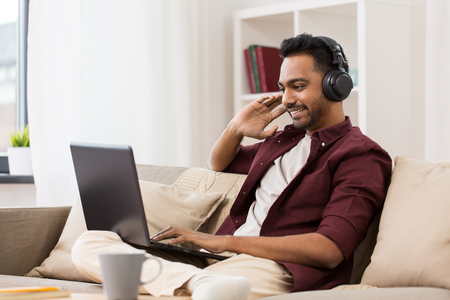 technology, leisure and people concept - happy man in wireless headphones with laptop computer listening to music at home Foto de archivo