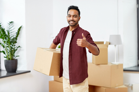 moving, people and real estate concept - happy indian man with boxes at new home showing thumbs up