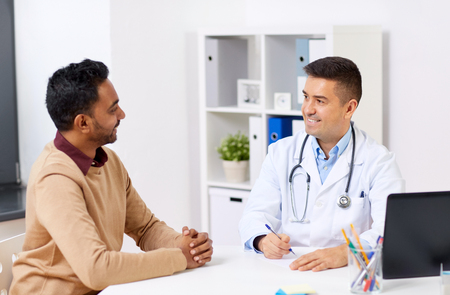 medicine, healthcare and people concept - happy doctor writing prescription for male patient at clinic