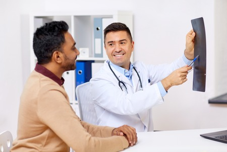 medicine, healthcare and people concept - happy doctor or surgeon showing x-ray to male patient at clinic