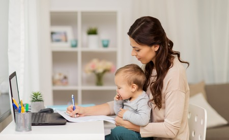 motherhood, multi-tasking, family and people concept - happy mother with baby, papers and laptop working at home Stock Photo