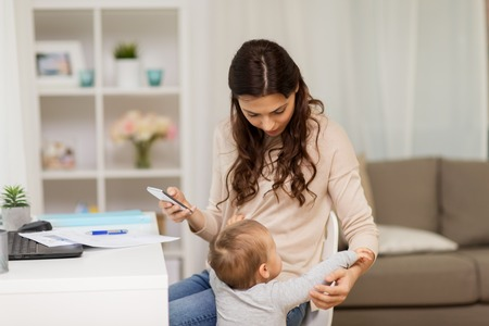 multi-tasking, freelance, family and technology concept - baby boy disturbing mother working at home