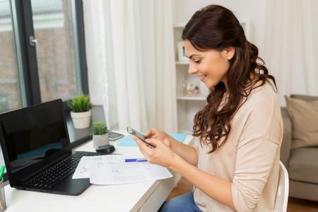 mensen, freelance en onderwijsconcept - gelukkige glimlachende vrouw met documenten en smartphone die thuis werken Stockfoto