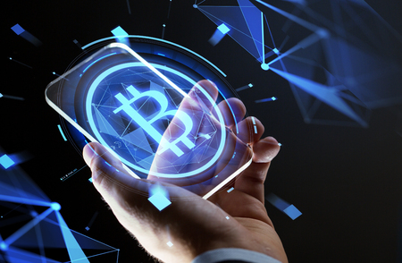 close up of hand with smartphone and bitcoin