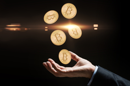 close up of businessman hand with bitcoins