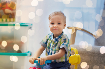 happy little baby boy driving ride-on car at home Stok Fotoğraf