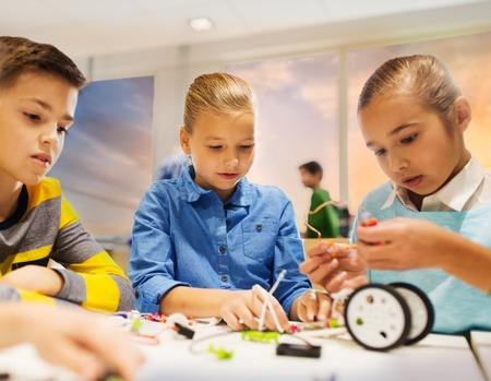 gelukkige kinderen bouwen van robots op school voor robotica