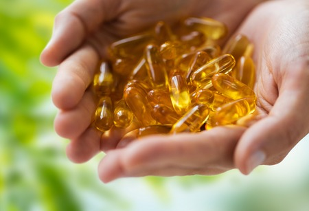 hands holding cod liver oil capsules Stock Photo