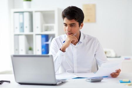 empresario en auriculares trabajando en oficina