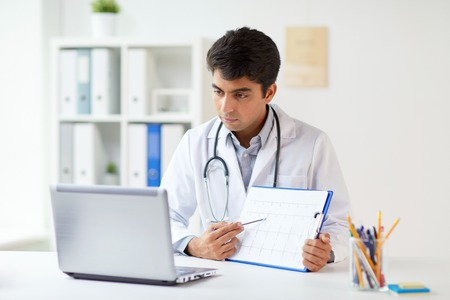 doctor with laptop and cardiogram at clinic