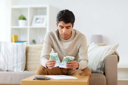 man counting money at home Stock Photo