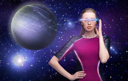 space, future technology and people concept - beautiful futuristic woman in virtual reality glasses transmitting signal to planet over stars background