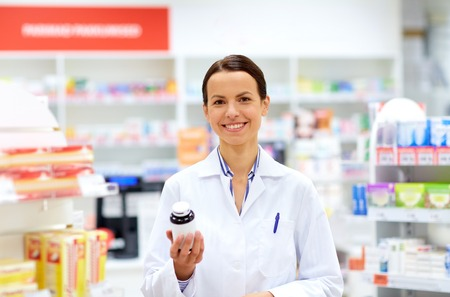 medicine, pharmaceutics, healthcare and people concept - happy female apothecary with drug at pharmacy