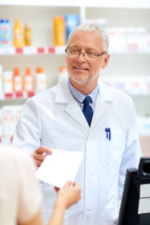 medicine, healthcare and people concept - senior apothecary taking prescription from customer at pharmacy