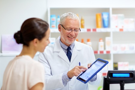 apothecary and customer with tablet pc at pharmacy Banque d'images