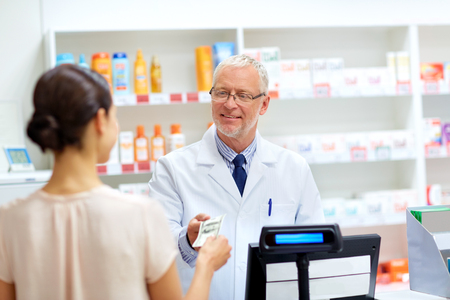 medicine, healthcare and people concept - female customer paying money to senior pharmacist at pharmacy cash register Archivio Fotografico