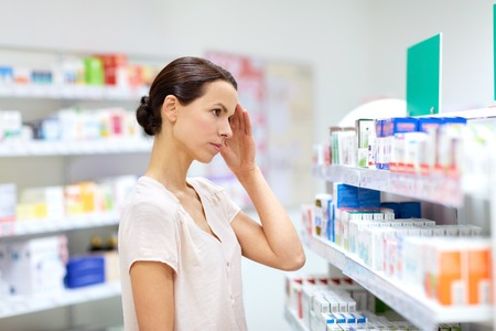 medicine, pharmaceutics, healthcare and people concept - female customer having headache choosing drugs at pharmacy