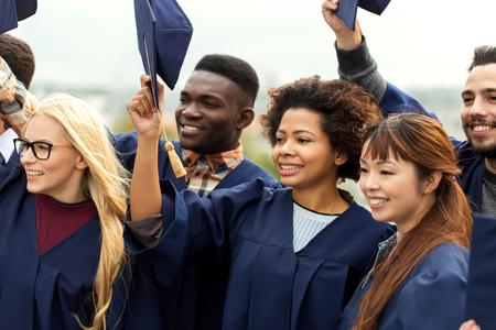 happy graduates or students waving mortar boards