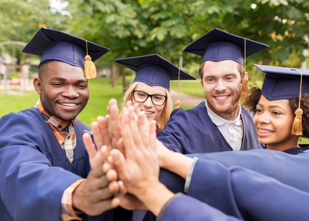education, graduation and people concept - group of happy international students in mortar boards and bachelor gowns making high five Reklamní fotografie