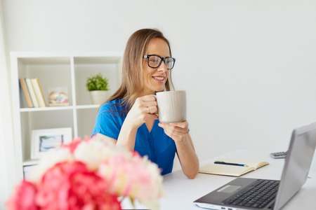 woman with laptop and coffee at home or office Banque d'images