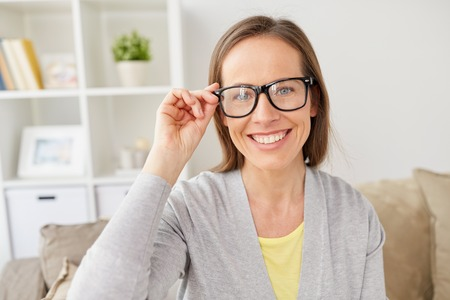 people, eyesight and vision concept - happy smiling middle-aged woman in eyeglasses at home