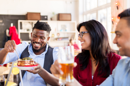 leisure, food and people concept - group of happy international friends eating and drinking at restaurant or bar