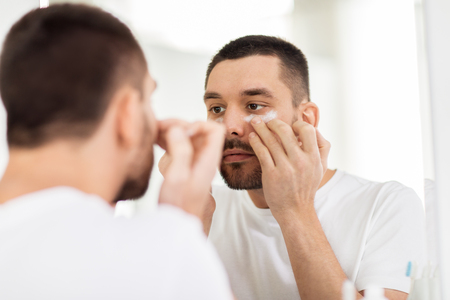 young man applying cream to face at bathroom