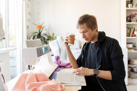 people, clothing and tailoring concept - fashion designer drinking coffee from disposable paper cup and reading book at studio