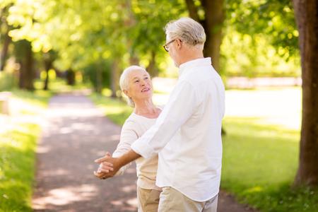 happy senior couple dancing at summer park Stock Photo