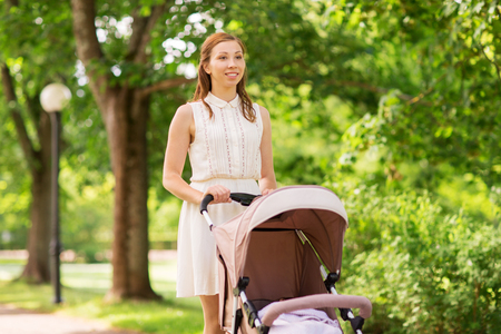 family, motherhood and people concept - happy mother with child sleeping in stroller walking at summer park Stock Photo - 93256920