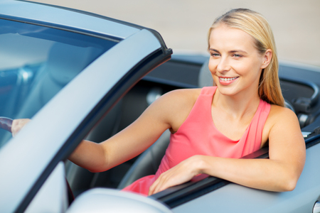 travel, road trip and people concept - happy young woman driving convertible car