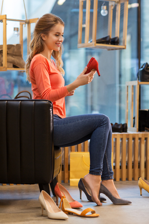 sale, shopping, fashion and people concept - young woman choosing high heeled shoes at store Banco de Imagens