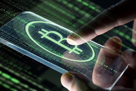 스마트 폰 및 bitcoin와 손을 가까이 스톡 콘텐츠