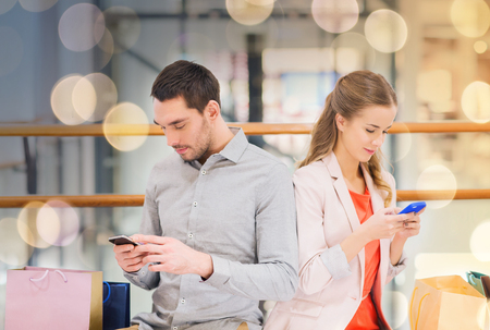 couple with smartphones and shopping bags in mall Banque d'images