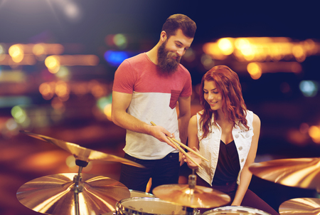 man and woman with drum kit at music store
