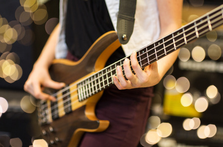 musical instruments, entertainment and people concept - close up of female musician playing guitar at music studio over lights background
