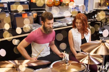 mensen, muziekinstrumenten en entertainmentconcept - gelukkige man en vrouw met drumstel bij muziekwinkel over lichten Stockfoto
