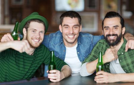 Menschen, Freundschaft und St. Patricks Day-Konzept - glückliche männliche Freunde, die Flaschenbier trinken und an der Bar oder im Pub umarmen Standard-Bild - 93404364