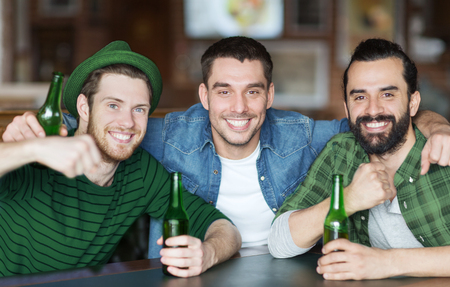 people, friendship and st patricks day concept - happy male friends drinking bottled beer and hugging at bar or pub Stock Photo