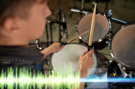 music, people, musical instruments and entertainment concept - male musician with drumsticks playing drum kit at concert or studio