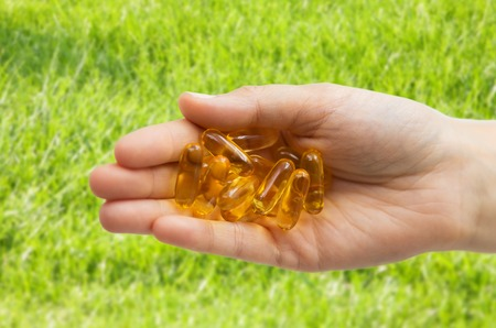 medicine, nutritional supplements and people concept - close up of hand holding cod liver oil capsules over grass background Banque d'images