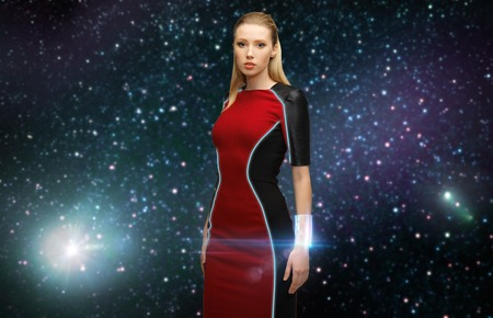 space, future technology and people concept - beautiful futuristic woman wearing transmitter bracelet over stars background
