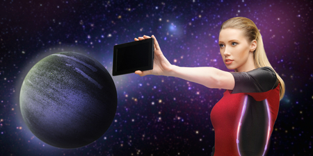 space, future technology and people concept - beautiful futuristic woman with tablet pc computer over planet and stars background