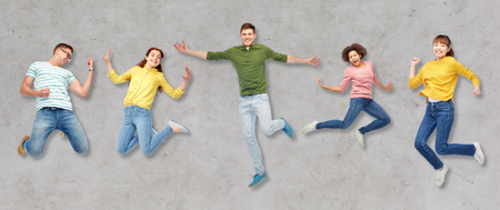 happiness, freedom, motion and people concept - smiling young international friends jumping in air over gray concrete background Stock Photo